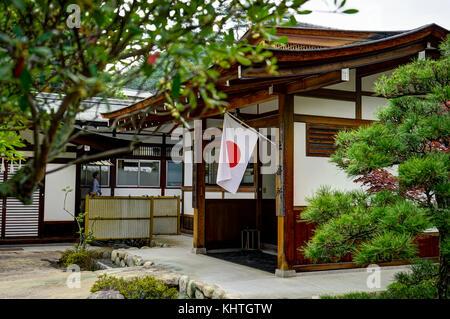 Miyajima Island, Hiroshima, Japan, October 2017 Japanese Traditional House with Flag - Stock Photo