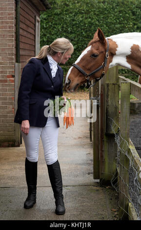 Smartly dressed female rider holding a bunch of carrots to tempt her Skewbald horse - Stock Photo