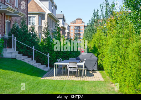 Beautiful exterior of newly built luxury home. Yard with green grass and walkway lead to ornately designed covered - Stock Photo