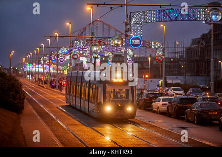 Blackpool tram running along the promenade at night with the Pleasure beach behind, in Lancashire - Stock Photo