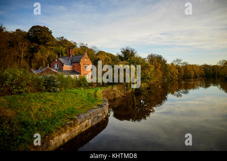 A Autumn landscape featuring a large brick house on the banks of the River Weaver in Northwich, Cheshire. - Stock Photo