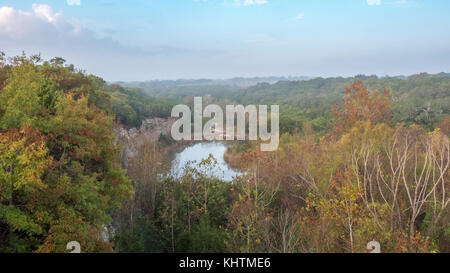 Aerial View of Lake Hidden inside Forest With Fog Over the Trees - Stock Photo