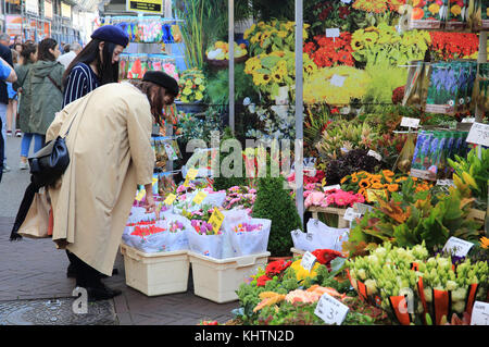 Friends shopping at the world famous floating flower market on the Singel canal, in Amsterdam in the Netherlands - Stock Photo