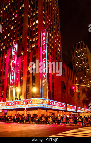 NEW YORK CITY - SEPTEMBER 28, 2017: View of busy night street scene outside Radio City Music Hall on Sixth Avenue - Stock Photo