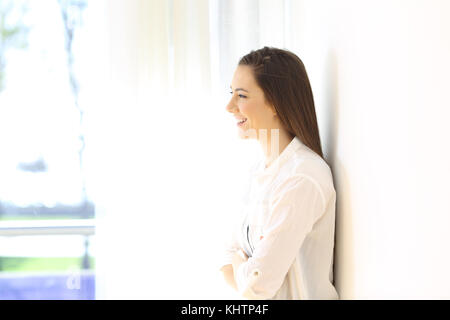 Side view portrait of a proud woman looking through a window at home - Stock Photo