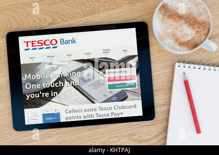 The Tesco Bank website features on an iPad tablet device which rests on a wooden table beside a notepad and pencil - Stock Photo