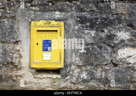 Vougeot, France - June 9, 2017: Old and vintage yellow french letterbox in France, the french public postal service - Stock Photo
