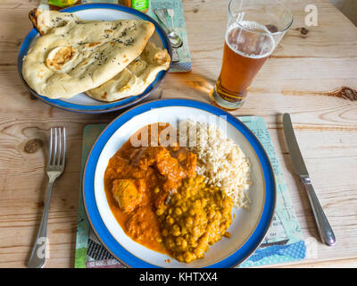 Indian Take-away food served at home Chicken Madras Curry, Tarka Dahl, Tandoori Naan, Basmati Brown Rice, Mango - Stock Photo