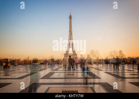 Blurred people on Trocadero square admiring the Eiffel tower at sunset, Paris, France - Stock Photo