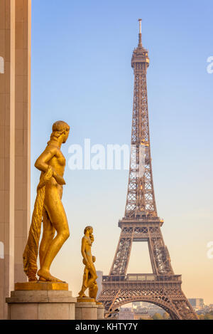 Golden bronze statues on Trocadero square, Eiffel tower in the background, Paris France - Stock Photo