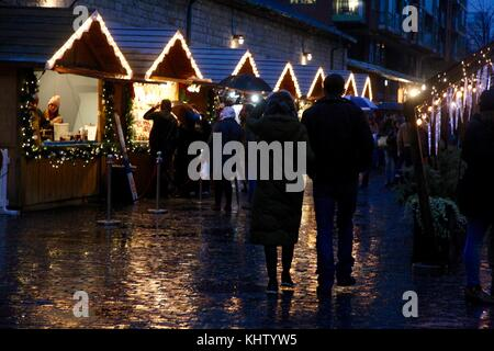 People walking through the Toronto Christmas market in the rain with the stalls lit up at night - Stock Photo