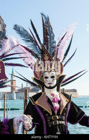 Venice Carnival 2017, man in elegant feathered headdress and mask posing in front of the lagoonand San Giorgio Maggiore - Stock Photo