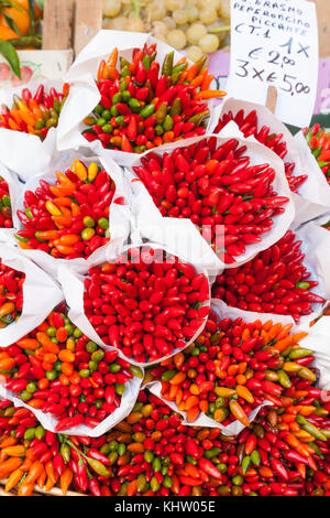 Bunches of fresh red hot chili peppers or peperoncini displayed on sale at Rialto Market, Venice, Italy. Local or - Stock Photo