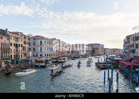 View from the Rialto Bridge, Venice,  Veneto, Italy at sunset with gondolas and boat traffic on a busy Grand Canal - Stock Photo
