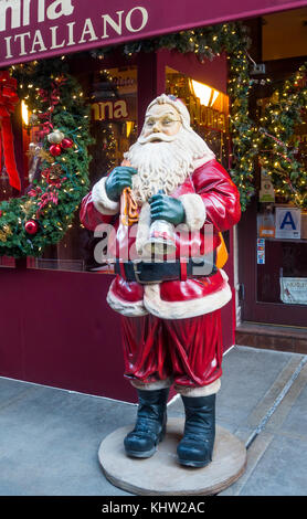A life-size Santa Claus figure outside an Italian restaurant in Little Italy, New York City - Stock Photo