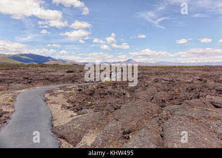 Tourists are hiking on an asphalt path on top of the lave flows of Craters of the Moon National Monument & Preserve - Stock Photo