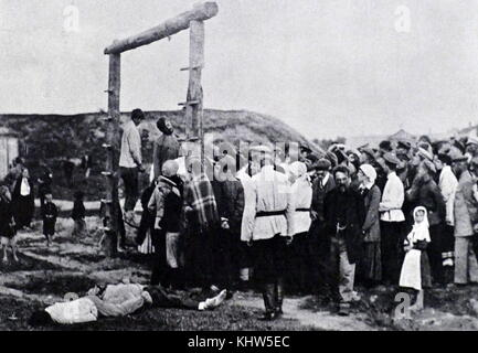 Photograph taken of a White Lynching party. After hanging Bolsheviks, the execution squad invites villagers to take - Stock Photo
