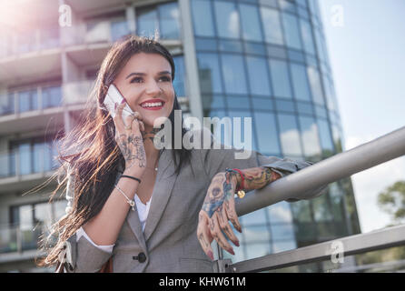 Businesswoman outdoors, using smartphone, smiling, tattoos on hands - Stock Photo