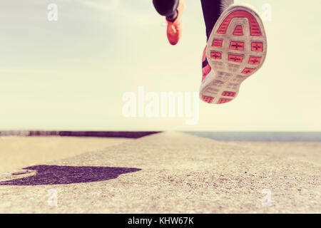 Young man running outdoors, mid air, low section - Stock Photo