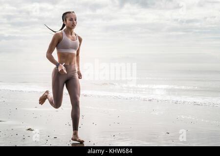 Young woman running along beach