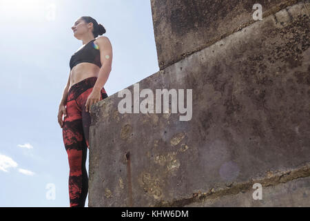Young female free runner looking out from sea wall - Stock Photo