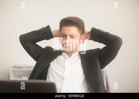 Young man working from home, staring at laptop - Stock Photo