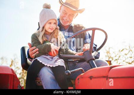 Farmer and granddaughter at pumpkin farm - Stock Photo