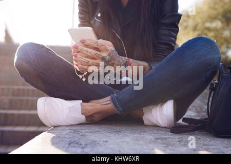 Young woman sitting on wall, using smartphone, tattoos on hand, low section - Stock Photo