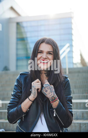 Portrait of young woman holding collars of jacket, smiling, tattoos on hands - Stock Photo