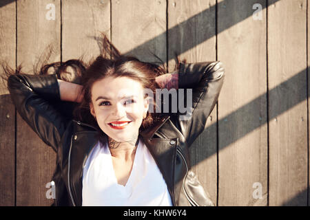 Portrait of young woman lying on wooden decking, hands behind head, smiling, overhead view - Stock Photo
