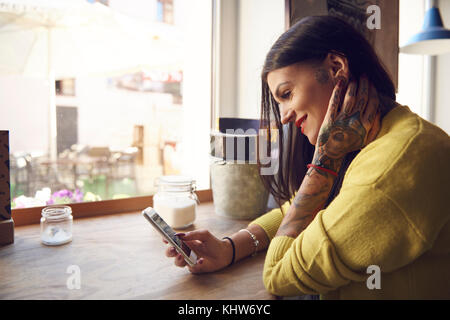 Young woman sitting in cafe, using smartphone, tattoos on arm and hand - Stock Photo