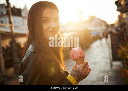Portrait of young woman holding ice cream, tattoos on hand - Stock Photo