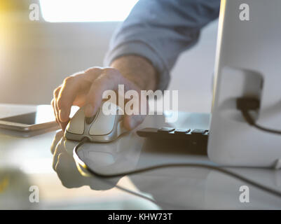 Businessman's hand on a computer mouse working in office - Stock Photo