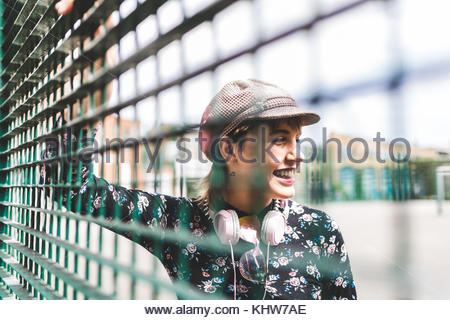 Retro styled young woman in baker boy hat behind wire fence - Stock Photo