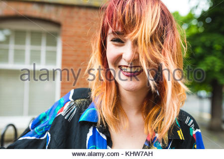 Portrait of young woman with dip dyed hair laughing - Stock Photo