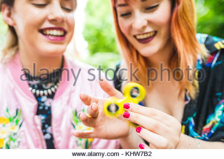 Two retro styled young women playing with fidget spinner in park - Stock Photo
