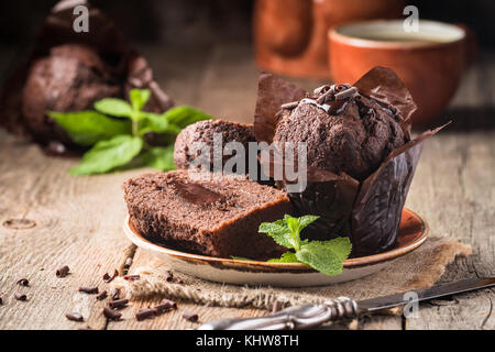 Homemade delicious chocolate muffins with mint and chocolate on wooden background close-up - Stock Photo