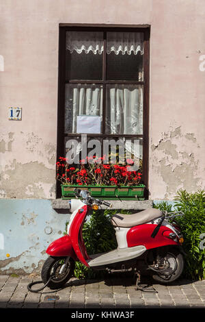 June 9, 2015 - Bruges, Belgium - A motor scooter rests against a windowsill on a side street in Bruges, Belgium. - Stock Photo