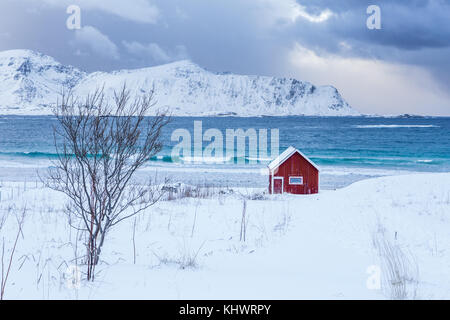 A typical house of the fishermen called rorbu on the snowy beach frames the icy sea at Ramberg Lofoten Islands, - Stock Photo