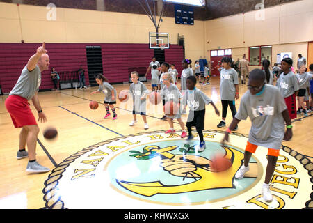 171111-N-RP435-075 SAN DIEGO (Nov. 11, 2017) A volunteer coach assists military youth with basketball fundamentals - Stock Photo