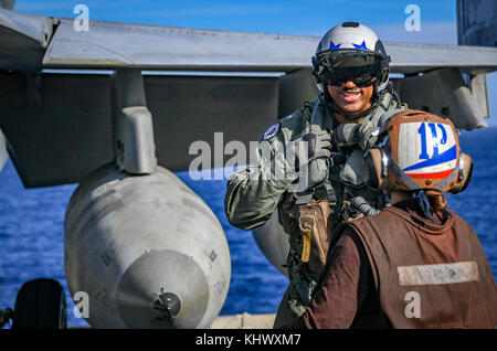 PACIFIC OCEAN (Nov. 14, 2017) Rear Adm. John Fuller, commander of Carrier Strike Group 1, converses with a Sailor - Stock Photo