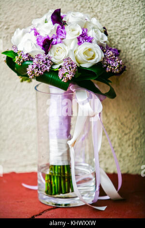 A purple and white bridal flowers bouquet in clear glass vase against white and red wall - Stock Photo