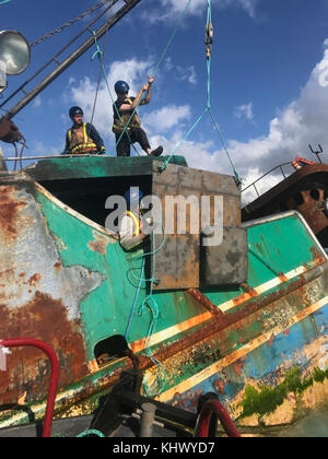 Members of the Pacific Paradise response team load a fabricated response hatch onto the vessel from a support boat - Stock Photo