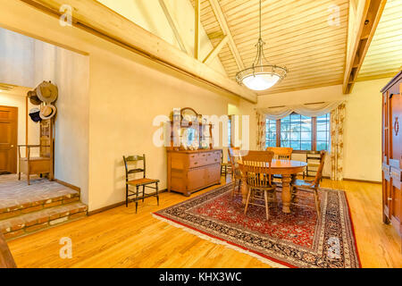 Bright, open and warm dining room with vaulted ceilings and rug. Wonderful California home in San Diego county. - Stock Photo