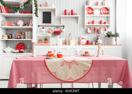 Interior light grey kitchen and red christmas decor. Preparing lunch at home on the kitchen concept. Focus on table - Stock Photo
