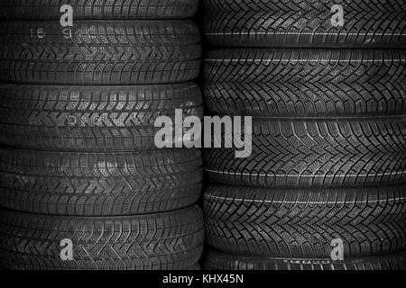 Tires for sale at a tire store - stacks of tires - Stock Photo