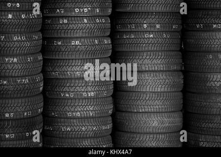 Tires for sale at a tire store - stacks of car tires - Stock Photo