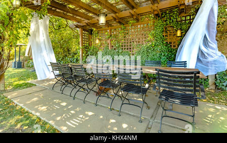 Eating area with some white drapes outside. Setup from a southern California wedding. Landscaped Garden with Wooden - Stock Photo