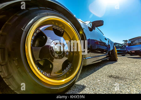 Perspective view of a black car with large golden rims in the front. Custom cars in Southern California summer 2017 - Stock Photo