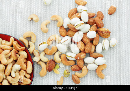 Salted cashew nut and almonds on tablecloth. - Stock Photo